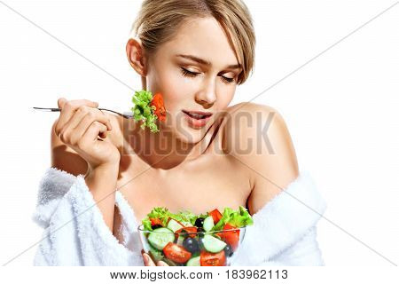 Healthy beauty. Attractive girl in bathrobe eating fresh salad and smiling. Portrait of blonde girl isolated on white background. Diet. Healthy lifestyle