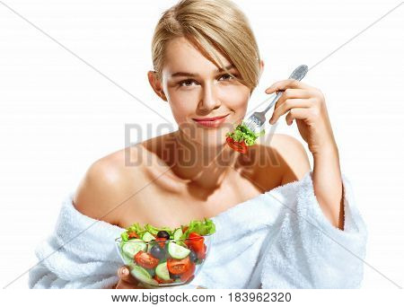 Smiling beautiful woman with salad at morning breakfast. Photo of young blonde in bathrobe isolated on white background. Diet. Healthy lifestyle