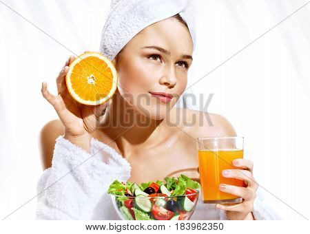 Beautiful young woman of the european appearance after taking a shower enjoying a healthy food. Portrait of blonde holding orange juice and orange fruit. Happy and healthy