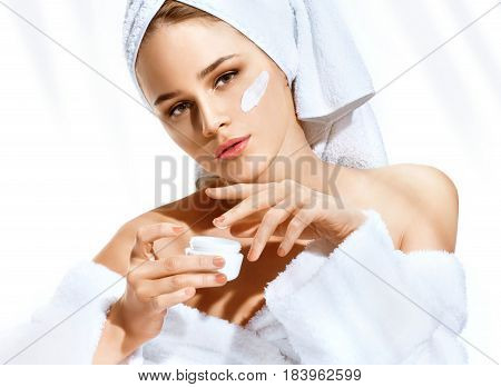 Applying moisturizer cream. Beautiful woman after bath cares about her face. Portrait of woman with perfect skin. Skin care concept