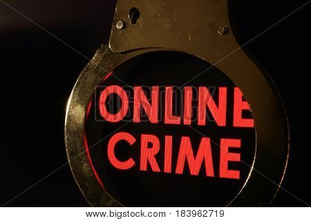 Words Online crime on a monitor and handcuffs.