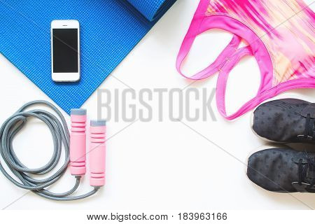 Overhead view of smartphone with yoga and sport equipments on white background