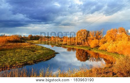 Autumn landscape -forest river with autumn golden tree at the bank. Autumn colorful forest nature - sunset autumn picturesque landscape with autumn river and yellowed autumn trees in the autumn evening. Soft filter applied.