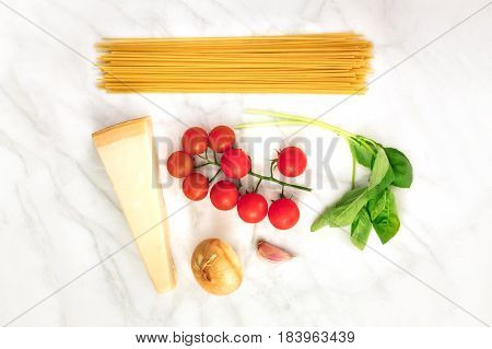 An overhead photo of basic pasta ingredients on a white marble table. Fresh cherry tomatoes, a slice of cheese, spaghetti, basil leaves, an onion, and a garlic clove, with a place for text