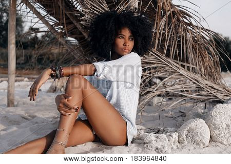 beautiful young african american girl sitting on sand at the beach