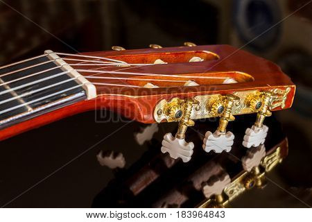 Guitar headstock on black reflecting surface close up with very shallow depth of field focus on tuning pegs