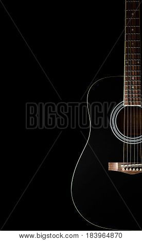 Classical black guitar on a black background with copy space. Isolated