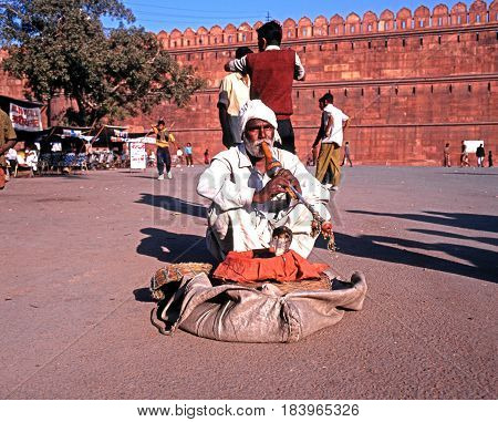 DELHI, INDIA - NOVEMBER 20, 1993 - Snake charmer tempting cobra snakes out of their wicker baskets outside the Red Fort Delhi Delhi Union Territory India, November 20, 1993.