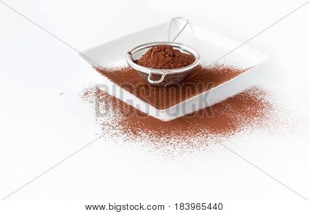 Close up of a metal sieve filled with cocoa powder on a white square porcelain plate. White background with copy space shallow depth of field and selective focus on the cocoa powder in the sieve.