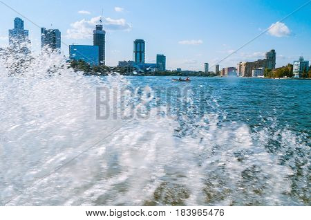 YEKATERINBURG RUSSIA -AUGUST 24 2013. Urban architecture landscape - modern business and administrative skyscraper buildings on the embankment of Iset river with splashing water wave on the foreground