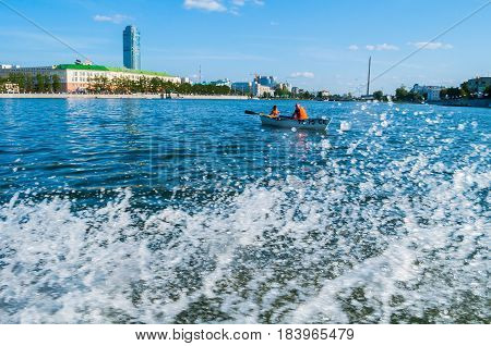 YEKATERINBURG RUSSIA -AUGUST 24 2013. Urban summer view- modern skyscraper buildings on the embankment of Iset river with focused splashing water wave on the foreground