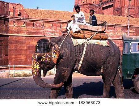 DELHI, INDIA - NOVEMBER 20, 1993 - View of the Red Fort with local men riding a painted elephant in the foreground Delhi Delhi Union Territory India, November 20, 1993.