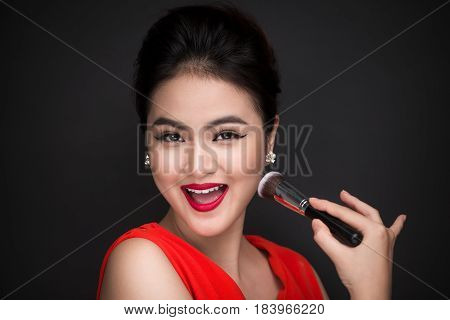 Cosmetic Powder Brush. Asian Woman Applying Blusher On Her Cheeks With Perfect Make-up And Red Lips