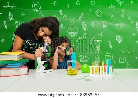 2 little indian girls studying science or biology using microscope in the classroom over green chalkboard background having science doodles drawn with chalk