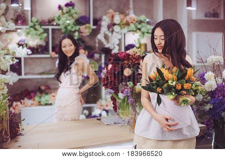 Beautiful asian florist girls making bouquet of flowers on table for sale against floral bokeh background in flower shop indoors. Two attractive asian females florists working in store. Playful fashion models in tender dresses posing and playing