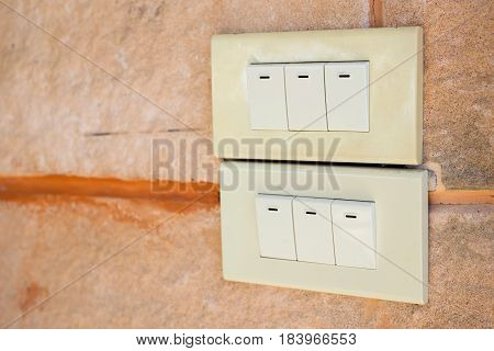 White light switch on yellow cement wall