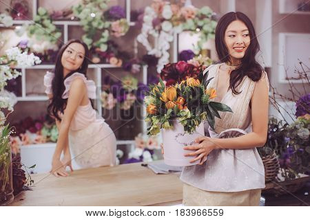 Beautiful asian florist girls making bouquet of flowers on table for sale against floral bokeh background in flower shop indoors. Two attractive asian females florists working in store. Playful fashion models in tender dresses posing and playing with flow