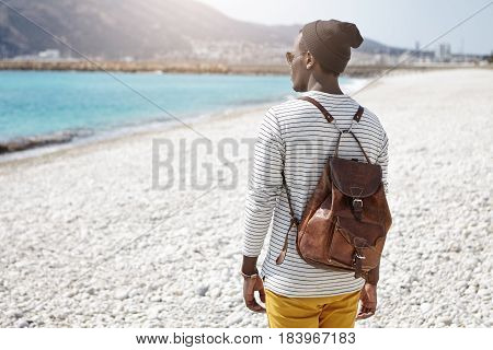 Back View Of African Backpacker Facing Sea In Trendy Clothes, Traveling Alone In European Summer Res