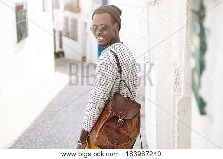 Back View Of Cheerful And Happy Black European Hipster With Knapsack On Shoulders Walking Down Narro