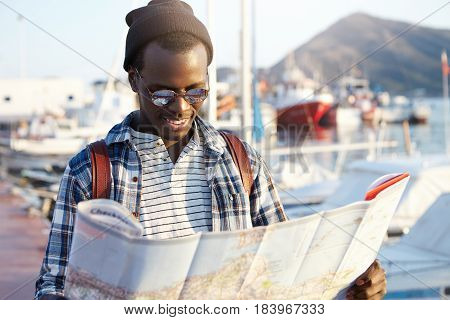 Trendy Looking African American Tourist With Backpack In Hat And Sunglasses Studying Directions Usin