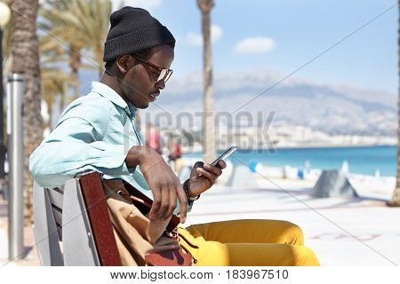 Sideview Outdoor Portrait Of Cheerful Stylish Young Afro American Man Sitting On Bench Along Promena