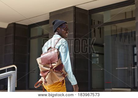 Cheerful Handsome Dark-skinned Male Tourist With Backpack Wearing Trendy Clothing About To Enter Mod
