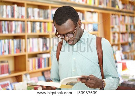 Stylish Young African American Male In Shirt And Eyewear Looking Through Book In Bookstore Standing