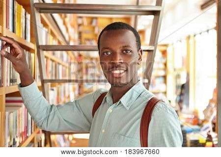 People, Leisure And Education. Curious Afro American Student Searching For Book In Library While Doi