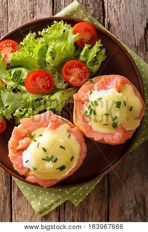Poached Eggs With Smoked Salmon, Hollandaise Sauce And Vegetables Close-up. Vertical Top View