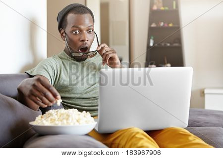 Surprised African Male Sitting On Couch At Home, Eating Popcorn And Watching Exciting Tv Show Online