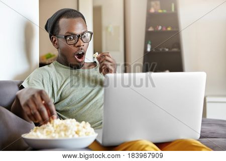 Omg. Excited Emotional Young Dark-skinned Man In Hat And Rectangular Glasses Sitting On Couch At Hom