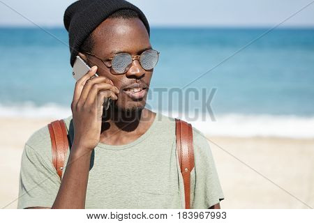 Picture Of Trendy Looking Black Male Tourist With Knapsack, Wearing Hat And Sunglasses On Sunny Weat