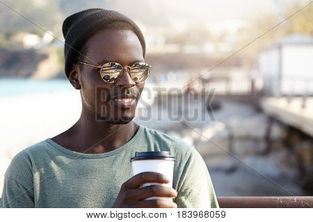 Attractive Young Afro American Man In Stylish Sunglasses Enjoying Fresh Takeaway Coffee In Paper Cup