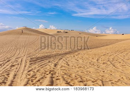 Sand dunes near Mui Ne. Group of off roads on top of dunes in the background. Sunny day with blue sky and clouds. Sand dune at Mui Ne Vietnam