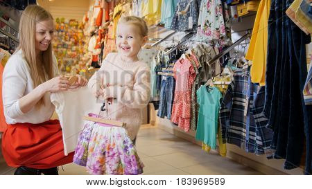 Young mother with blonde daughter buying kids clothes in store, telephoto