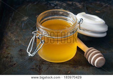Full honey pot and honey stick on dark