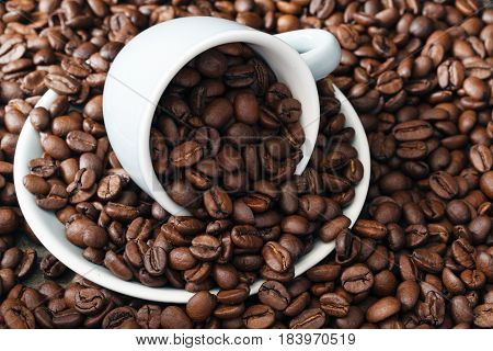 scattering of roasted coffee beans with cup