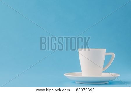 Modern Stylish White Coffee Cup Or Mug On A Plate On A Blue Background