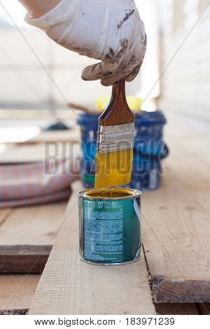 The worker puts a brush with a wooden handle into the jar with a yellow paint.
