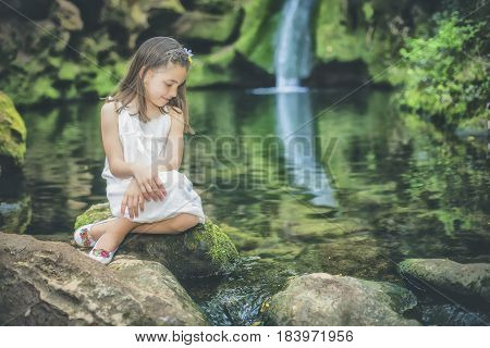 Little girl looks at the water sitting next to the bed of a river