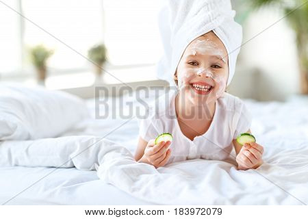 happy child girl in towel with mask on face and cucumber