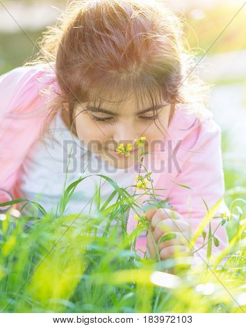 Portrait of a little girl enjoying flower aroma, having fun on fresh green grass field in spring sunny day, cute child with pleasure spending time outdoors
