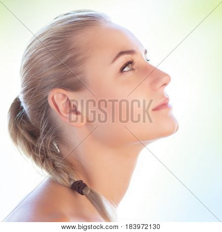 Profile portrait of a beautiful blond girl with pigtail hairstyle isolated on clear background, perfect clean skin, natural makeup, authentic beauty