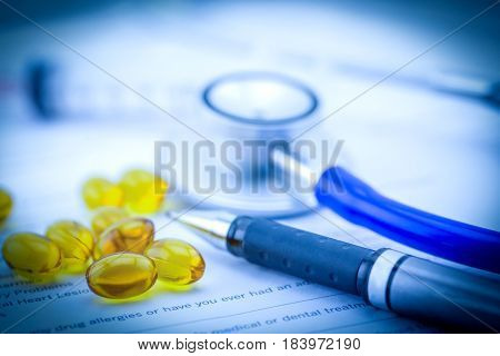 Medical Questionnaire, Stethoscope, Pen And Fish Oil Capsules With Document In Blue Tone