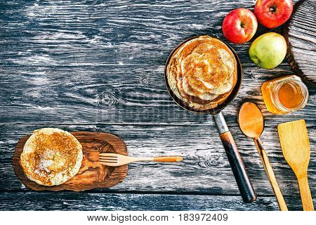 Apple pancakes with cinnamon and honey on textured wood boards. Fresh apples and wooden tableware. Top view