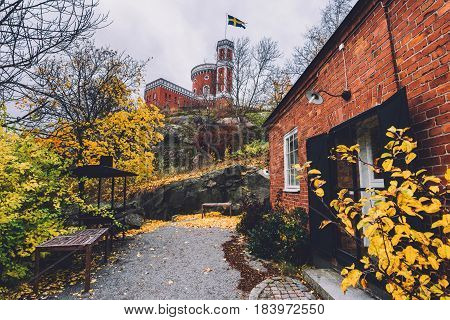 Kastellet fortress, small brick citadel located on Kastellholmen island. Autumn Stockholm scene with city public park and famous tower with swedish flag.