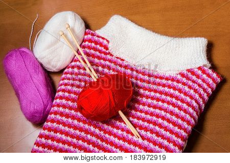 Knitted sweater with knitting needles and wool on wooden background