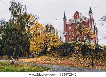 Admiralty House, golden trees and fallen leaves on Skeppsholmen islet in Stockholm by autumn cloudy day. Amiralitetshuset building near Skeppsholm bridge.