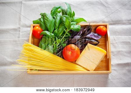 Green and purple basil chunk of parmesan cheese raw cappellini and tomatoes on wooden tray