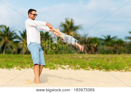 happy family father turns baby son on the beach